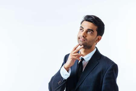 Retrato de un apuesto hombre de negocios con un dedo en la barbilla. aislado sobre fondo blanco Foto de archivo