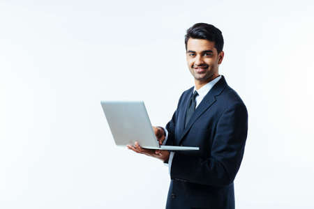 Portrait of a confident young man entrepreneur in business suit holding a laptop and smiling at camera,  isolated on white background 免版税图像