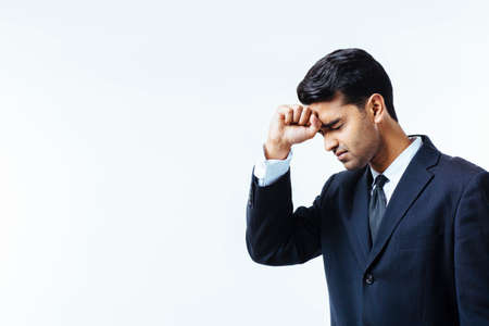 Portrait of a handsome businessman holding his head in disbelief, in pain or meditating,  isolated on white background Stock Photo
