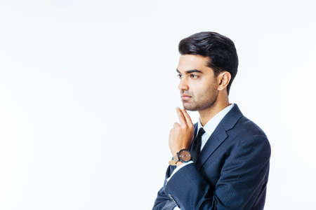 Close up portrait of a handsome businessman in suit and tie thinking with hand on mouth and looking to the side, isolated on white studio background