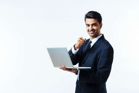 Portrait of a confident young man entrepreneur in business suit holding a laptop and pointing at camera,  isolated on white background Archivio Fotografico