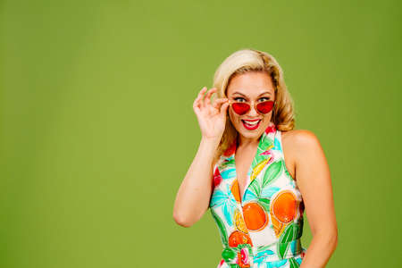 Flirty blonde woman peeking from under her red sunglasses, isolated on green studio background