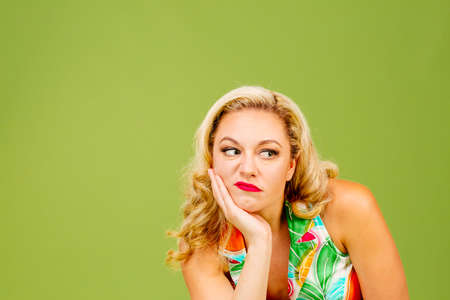Portrait of an envious woman in bad mood looking right, isolated on green studio background