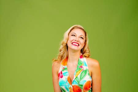 Donna bionda con un grande sorriso felice guardando in alto, isolato su sfondo verde studio
