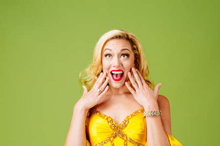 A very excited blonde looking up with hands by face, isolated on green studio background