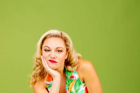 Portret van een verveelde en ongelukkige blonde vrouw, geïsoleerd op groene studioachtergrond