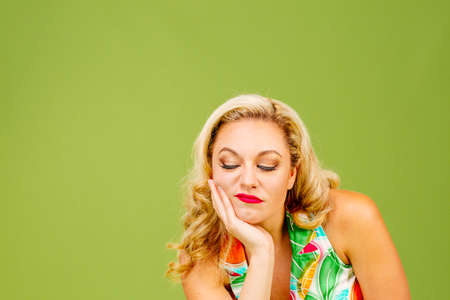 Portrait of a grumpy blonde woman looking down, isolated on green studio background Stock Photo