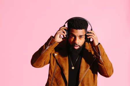 Stylish, handsome and cool African American man with beard, listening to music, isolated on pink studio background Stock fotó