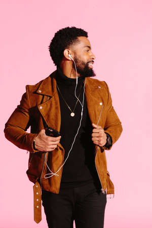Stylish, handsome and cool African American man with beard, listening to music, isolated on pink studio background Stock Photo