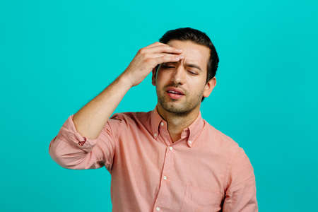 Portrait of a young adult man with a headache,  isolated on blue studio background