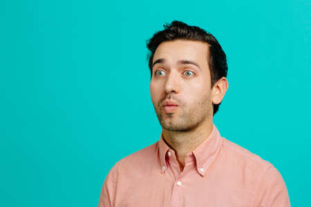 Portrait of a young adult man making funny faces,  isolated on blue studio background 版權商用圖片