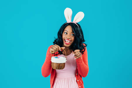 Portrait of a happy smiling mother with Easter eggs basket and bunny ears pointing at something, isolated on blue background