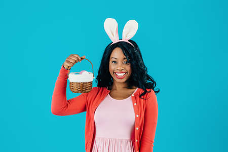 Portrait of a happy smiling mother with Easter eggs basket and bunny ears, isolated on blue background