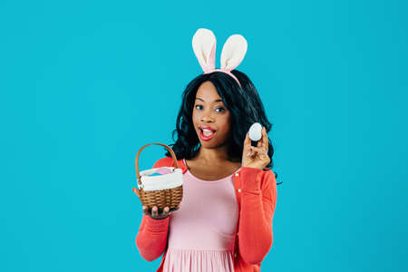 Portrait of a young mother with Easter eggs basket and bunny ears ready to hide painted egg, isolated on blue background