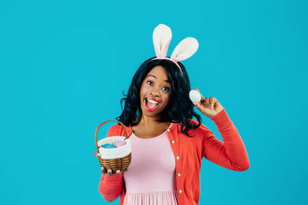Portrait of an excited mother with Easter eggs basket and bunny ears, isolated on blue background