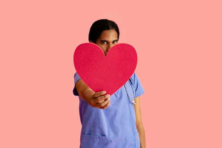 Studio portrait of a male doctor or nurse wearing blue scrubs holding heart cutout