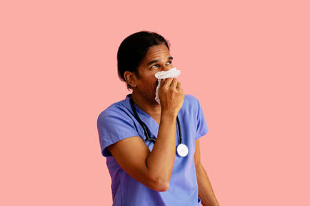 Studio portrait of a sick male doctor or nurse wearing blue scrubs and stethoscope blowing nose and looking up 版權商用圖片