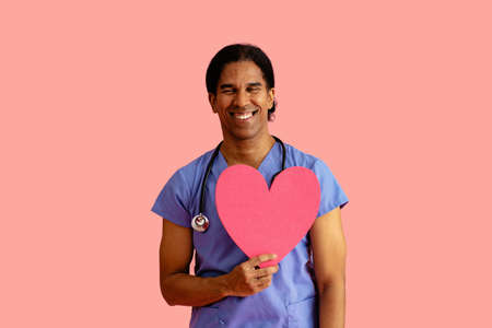 Studio portrait of a smiling male doctor or nurse wearing blue scrubs and stethoscope and holding heart cutout