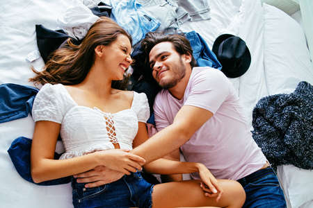 Portrait of a happy young couple lying on a bed with clothes, smiling while holding each other