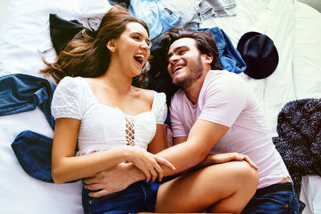 Portrait of a happy young couple lying on a bed with clothes, laughing while holding each other