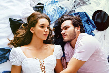 Portrait of a serious young couple lying on the bed with clothes and hats, thinking and talking