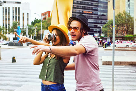 Portrait of young couple traveling and taking photo while pointing at monument on street of Mexico City center