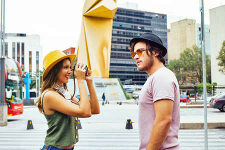 Portrait of a young couple traveling and taking a photo on street of Mexico City center