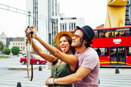 Portrait of a laughing young couple having fun taking selfie on street of Mexico City center near Caballito de la Loteria 版權商用圖片