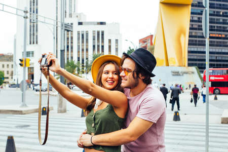 Portrait of a laughing young couple having fun taking selfie on street of Mexico City center 版權商用圖片