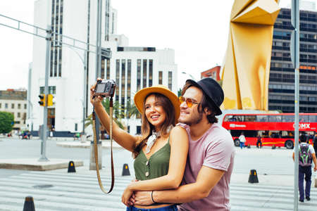 Portrait of a smiling young couple having fun taking selfie on street of Mexico City center