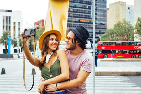 Portrait of a smiling young couple having fun taking selfie  looking at each other on street of Mexico City center