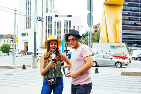 Portrait of happy young couple of tourists checking phone on street of Mexico City center