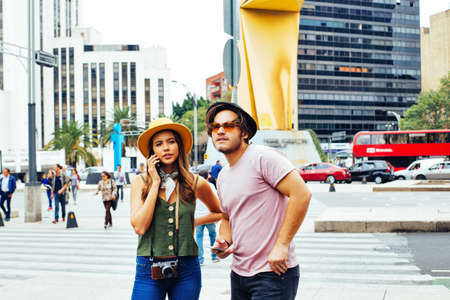 Portrait of young couple of tourists  with camera talking on phone on street of Mexico City center