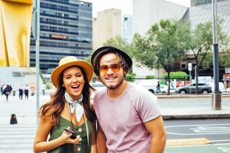 Portrait of happy young couple of trendy tourists with hats smiling at the camera in Mexico City