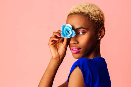 Portrait of  a beautiful young woman covering eye with blue rose flower, with trendy fresh makeup of pink lips and eyeliner