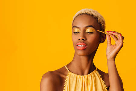 Portrait of a beautiful young woman applying yellow eyeshadow make up to her eyes, looking down