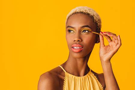 Portrait of a beautiful young woman applying yellow eyeshadow make up to her eyes 版權商用圖片