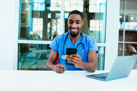 Portrait of a friendly male doctor or nurse wearing blue scrubs uniform and stethoscope sitting at desk with laptop in hospital checking mobile phone 版權商用圖片
