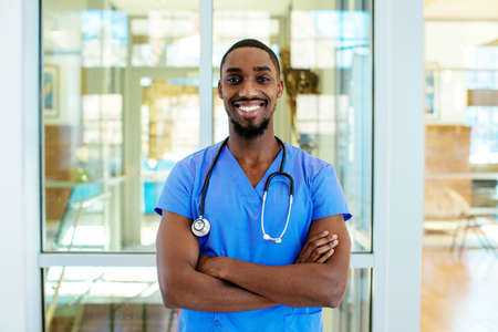 Portrait of a friendly male doctor or nurse wearing blue scrubs uniform and stethoscope, with arms crossed in hospital