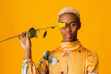 Portrait of  a beautiful young woman covering eye with yellow rose flower, with trendy fresh makeup of orange lips and yellow eye shadow