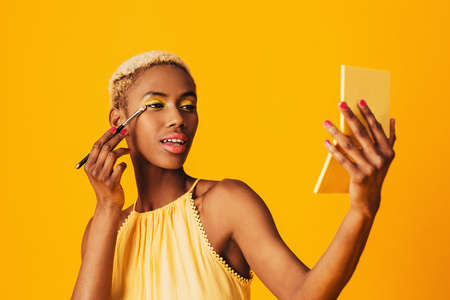 Portrait of a beautiful young woman applying yellow eye shadow make up to her eyes and holding compact mirror