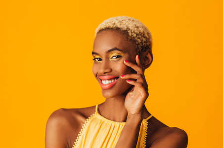 Beauty portrait of a happy young woman with bright yellow eye shadow make up and bold pink orange lips smiling at camera