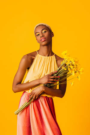 Portrait of  a beautiful young woman holding bouquet of yellow summer daisy flowers 版權商用圖片