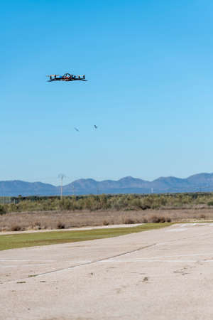 Professional drone flying over the airfield in hover Stock Photo