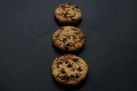 Three chocolate chip cookies in vertical line on black background.