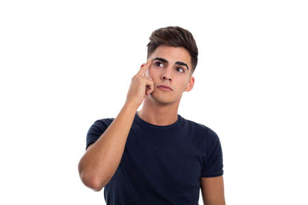 Handsome and thoughtful young man in a photo studio. He is touching his head with his hand. He is wearing a tight blue t-shirt Foto de archivo