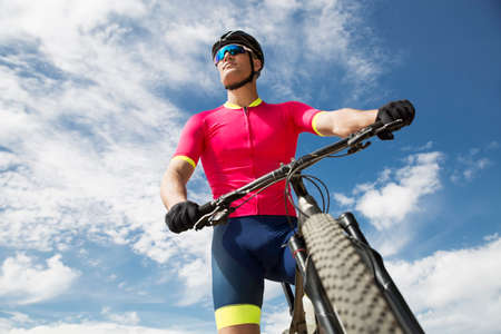 Young cyclist riding a bike across a countryside full of green trees. The sky is blue and cloudy. The cyclist is dressed with professional cyclist clothes. the clothes are pink, blue and yellow.