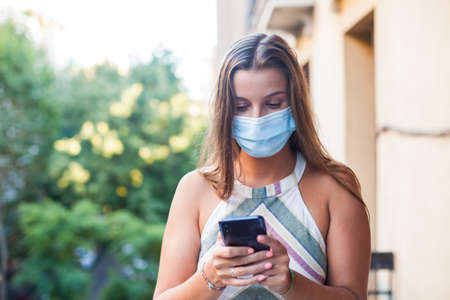 Beautiful woman wearing protective mask using a smart phone from her terrace Stock Photo