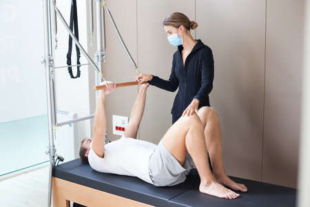 young man wearing mask doing pilates exercise on reformer with his female instructor during covid-19