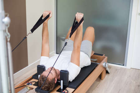 young man training on pilates reformer bed